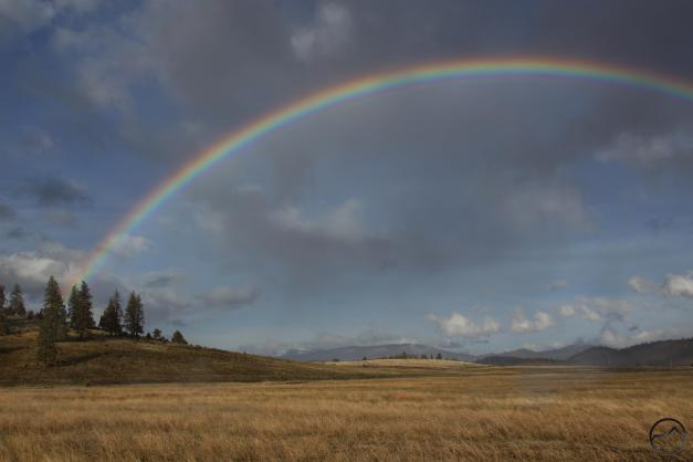 A rainbow arcs high above the Cascade Crest and the Shasta Valley.
